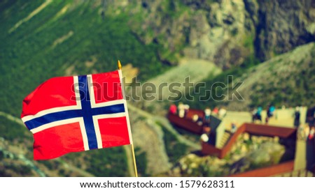 Trollstigen mountain road landscape in Norway, Europe. Norwegian flag waving and many tourists people on viewing platform in background. National tourist route. #1579628311
