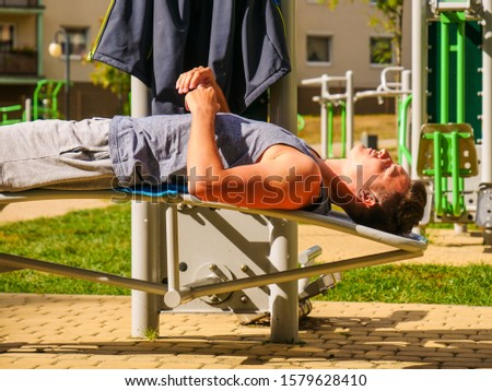 Sportsman relaxing after outdoor workout at street exercise machines for strength exercises. Fit man feeling healthy enjoying sun #1579628410