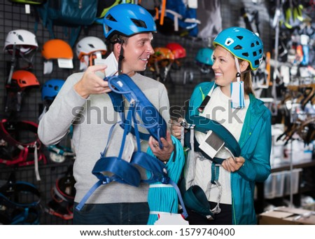 Young couple of customers holding sports equipment in sports store  #1579740400