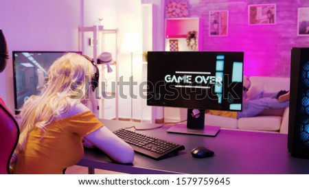 Sad blonde because she lost on a shooter game. Girl playing games and sitting on gaming chair. #1579759645