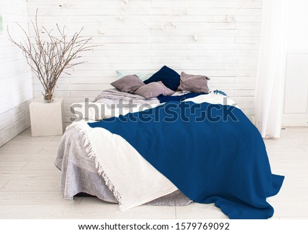 light, white, spacious bedroom with a large bed, in the Scandinavian style. Mockup and free space for text and pictures. color of the year pantone classic blue 2020