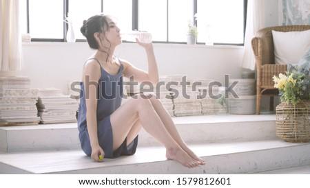 Beautiful woman drinking plastic bottle of water #1579812601