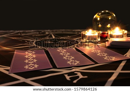 Tarot cards on  table with a crystal ball and burning candles in the background.Tarot reader or Fortune teller reading  tarot cards and forecasting concept.Mystic and darkness background. #1579864126
