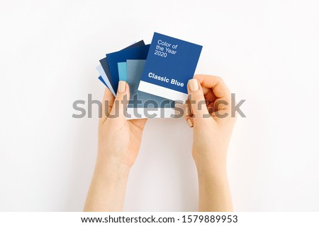 Female hand holding color of the year 2020 - Classic Blue with fashion colour swatches. Color trend palette.  Royalty-Free Stock Photo #1579889953
