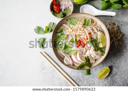 Traditional Vietnamese soup- pho ga in bowl with chicken and rice noodles, mint and cilantro, red onion, chili, bean sprouts and lime on grey background.  Asian food. Copy space. Top view  Royalty-Free Stock Photo #1579890622