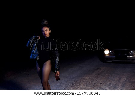 a young slender  girl in a leather jacket and bodysuit goes with a bottle of alcohol on an abandoned sandy road.at night in the light of car headlights and street lights #1579908343