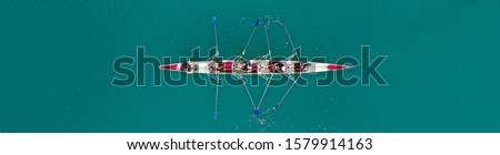 Aerial drone top down ultra wide panoramic view of sport canoe rowing synchronous athletes competing in tropical exotic lake Royalty-Free Stock Photo #1579914163