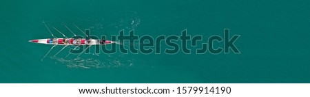Aerial drone top down ultra wide panoramic view of sport canoe rowing synchronous athletes competing in tropical exotic lake Royalty-Free Stock Photo #1579914190