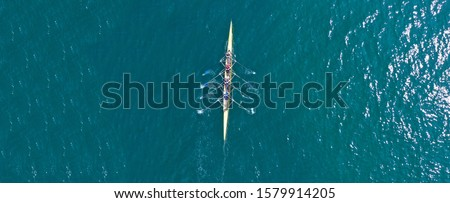 Aerial drone top down ultra wide panoramic view of sport canoe rowing synchronous athletes competing in tropical exotic lake Royalty-Free Stock Photo #1579914205