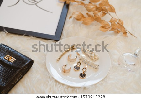 Women's fashion accessories in form of marble earrings and golden pearl hair clips on white plate bordered with bottle of perfume, bag and picture frame on white fur rug. Top view fashion, beauty.