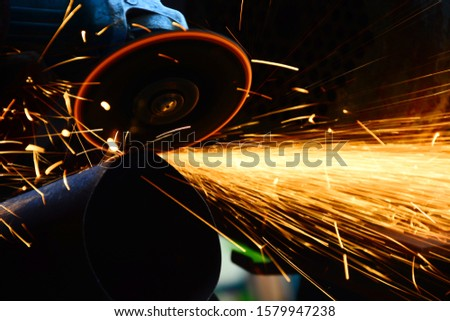 Sawing metal.Metal cutting with a handheld machine. Royalty-Free Stock Photo #1579947238