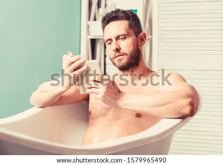 Relaxed guy reading book while relaxing in hot bath. Relax at home. Total relaxation. Personal hygiene. Nervous system benefit bathing. Relax concept. Man muscular torso relax bathtub and read book. #1579965490