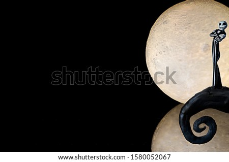 A die cast from the Nightmare Before Christmas in front of a 3D printed moon. Isolated in black and room for text. Royalty-Free Stock Photo #1580052067