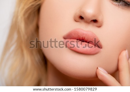Beautiful lips Close-up. Makeup. Lip matte lipstick. Sexy lips. Part of face, young woman close up. perfect plump lips bodily lipstick.  peach color of lipstick on large lips. Perfect makeup.          #1580079829