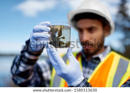 Marine biologist analysing water test results and algea samples Royalty-Free Stock Photo #1580113630