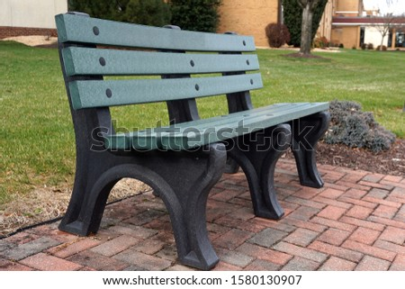 park bench set on a bed of bricks provides a resting place for walkers #1580130907