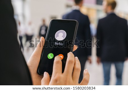 Businesswoman gets a Phone call from a stalker. Stalking or bullying with smartphone concept. Stalker caller, scammer or stranger. Woman answering to incoming call. Ex boyfriend with fake identity. #1580203834