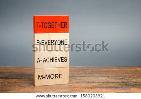 Wooden blocks with the word Together, Everyone, Achieves, More. Teamwork and team concept. Community, support, partnership. Achieving a common goal. Cooperation and business strategy #1580203921