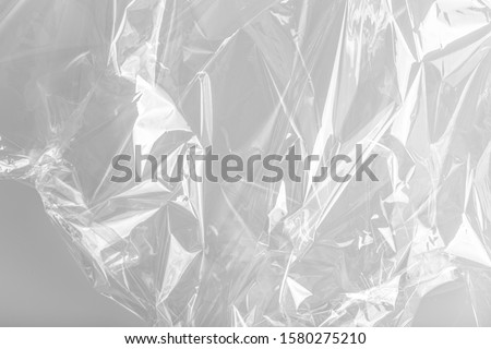 Close up picture on a plastic transparent cellophane bag on white background. The texture looks blank and shiny. The plastic surface is wrinkly and tattered making abstract pattern. #1580275210