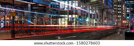 Busy city street at night with light streaks from vehicles panoramic #1580278603