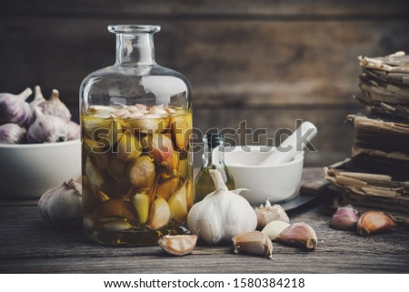 Garlic aromatic flavored oil or infusion bottle and garlic cloves. Mortar, old recipe books, kitchen knife. Garlic cooking.  #1580384218