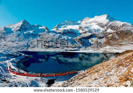 A Bernina Express train traveling along the lake shore of Lago Bianco & alpine mountains towering under blue sky in background after a snowfall in autumn, near Ospizio Bernina, in Grisons, Switzerland Royalty-Free Stock Photo #1580529529