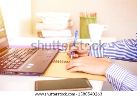 Businesswoman with laptop writes on a document at office #1580540263