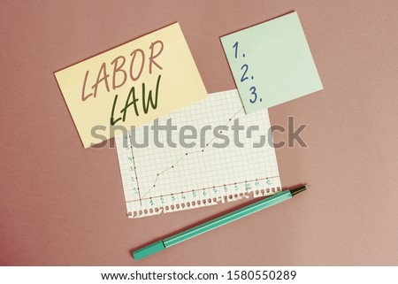 Writing note showing Labor Law. Business photo showcasing rules relating to rights and responsibilities of workers Stationary and note paper math sheet with diagram picture on the table.