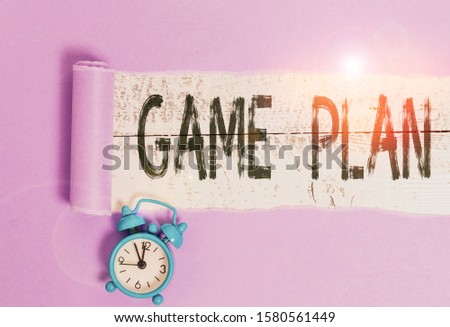 Word writing text Game Plan. Business concept for strategy worked out in advance in sport politics or business Alarm clock and torn cardboard placed above a wooden classic table backdrop. #1580561449