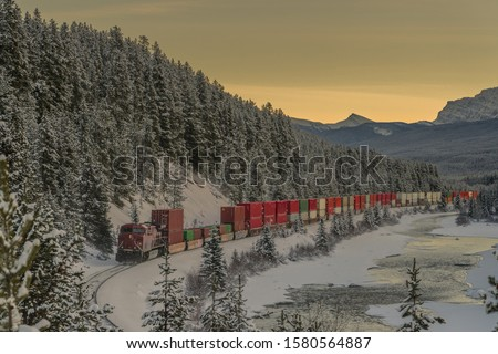 Freight train with containers after picturesque Morant's curve on a cold winter evening with sun just setting behind majestic mountains. #1580564887