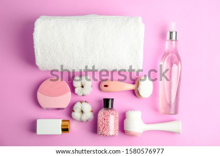 Flat lay composition with face cleansing brushes on violet background. Cosmetic tools