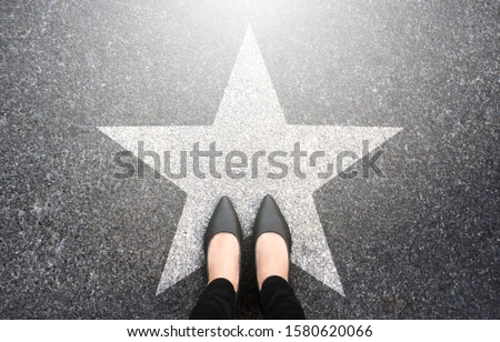 Success in business design concept. Businesswoman standing on street road background. Top view. Selfie of feet in black high heels shoes and white star symbol on pathway floor. New talent or champion. Royalty-Free Stock Photo #1580620066