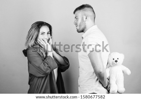 Surprising her. Handsome man and pretty girl in love. Man and woman couple in love. Romantic surprise. Valentines day holiday. Surprise for sweetheart. Soft toy teddy bear gift. Surprise gift concept. #1580677582