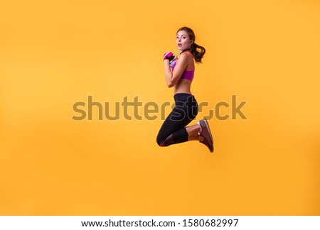 Inspired woman training in headphones. Slim caucasian girl doing excersizes.Woman in sportswear running over yellowbackground. Full length shot of healthy young caucasian woman sprinting. Copy space. #1580682997