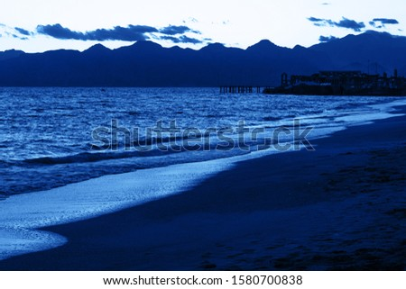 Dusk on the beach of the Mediterranean and mountains range on the horizon. Pantone 2020 Classic Blue color in nature. #1580700838