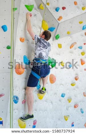 Sportsmen climbs boulder in a gym. A successful man climbing on climbing wall. #1580737924