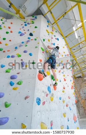 Sportsmen climbs boulder in a gym. A successful man climbing on climbing wall. #1580737930