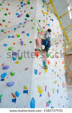Sportsmen climbs boulder in a gym. A successful man climbing on climbing wall. #1580737933