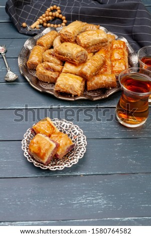 Top view of big metal tray with turkish baklava on planked wooden table