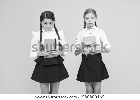 Unhappy bookworms. Unhappy little schoolchildren on yellow background. Adorable small girls with unhappy emotions holding books. Unhappy because of bad marks. #1580800165
