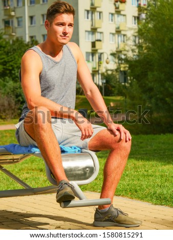 Sportsman relaxing after outdoor workout at street exercise machines for strength exercises. Fit man feeling healthy enjoying sun #1580815291