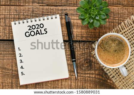 New year goals 2020 on desk. 2020 goals list with notebook on wooden table. High resolution photography, top view - business concept.