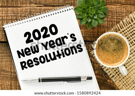 New year resolutions 2020 on desk. 2020 goals list with notebook on wooden table. High resolution photography, top view - business concept.