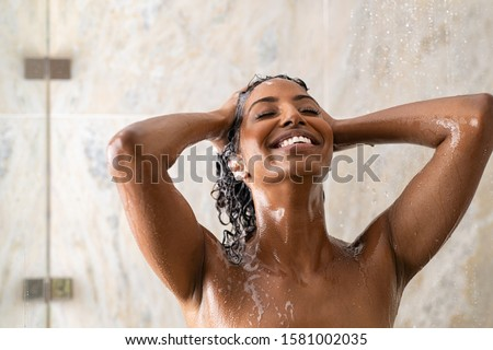 Young woman washing hair in shower at luxury spa. Woman washing her curly hair with shampoo and a lot of lather. Carefree black girl taking a long hot shower washing her hair in a modern bathroom. #1581002035