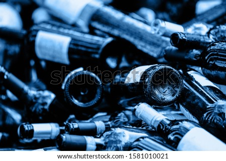 A large heap of empty wine bottles. Garbage. Recycle concept. Color of the year 2020 classic blue toned. Ecology #1581010021