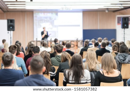 Business and entrepreneurship symposium. Female speaker giving a talk at business meeting. Audience in conference hall. Rear view of unrecognized participant in audience. #1581057382