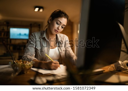 Female student taking notes while learning at night at home.  #1581072349