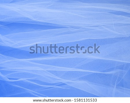 Lightweight fabric mesh lace on blue paper, texture of the fabric is beautifully draped background. Abstract soft chiffon veil backdrop. Bride concept. Classic blue color of the year 2020 #1581131533