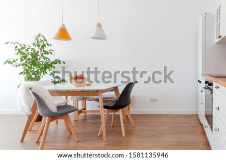 Modern interior of cozy kitchen, dining room, white furniture, lamps above wooden table, chairs, apples, bowl. Concept decor, design, advert, credit, mortgage, home for young family, magazine cover Royalty-Free Stock Photo #1581135946
