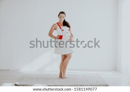 a pregnant woman has fun laughs white #1581149077